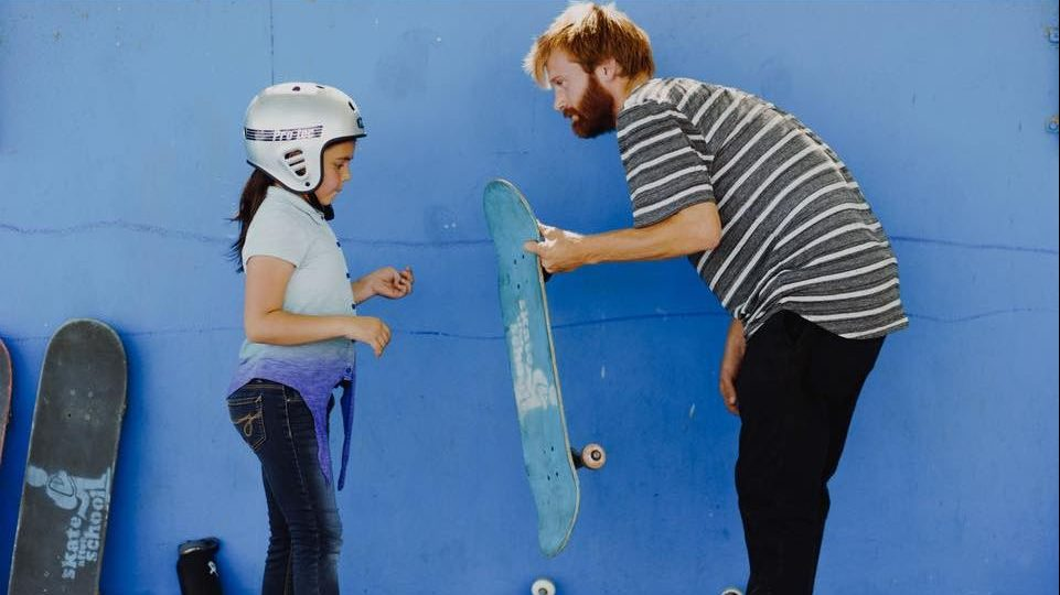 Image: Man handing a participant a skateboard that has the Skate After School logo on it