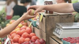 Image: at a market one person hands an apple to another