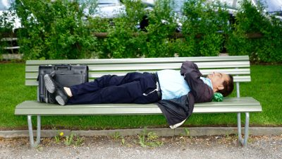 Image: business man sleeps on a park bench