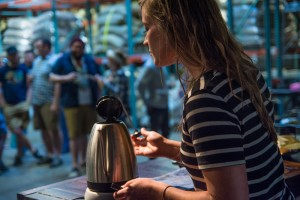 Barista measuing water temperature in her kettle