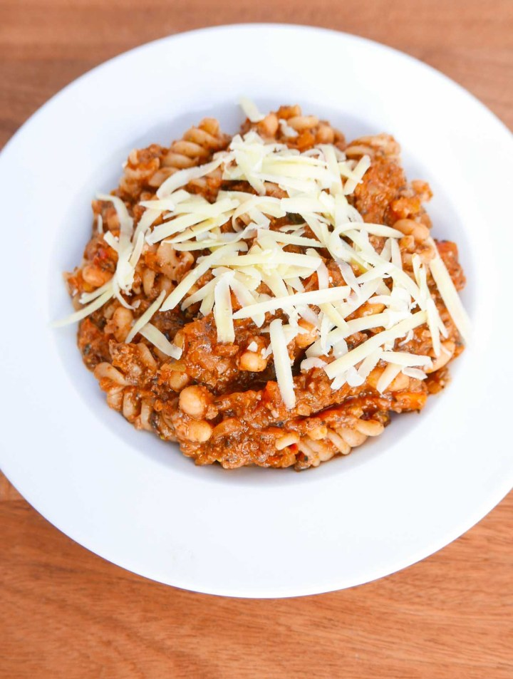 Cowboy dinner - a mince, vegetable and pasta dish with baked beans in a white china bowl with grated cheese.