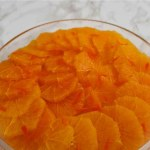 Oranges in Liqueur. Sliced oranges arranged in a shallow glass dish with slivers of orange peel decorating