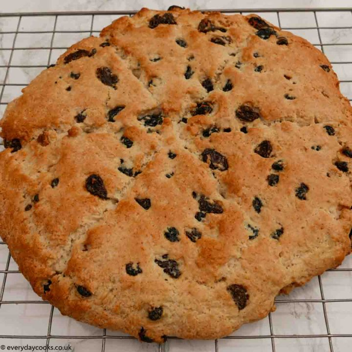 A whole fruit tea scone cooling on a wire rack on a marble kitchen worktop.