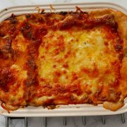 A dish of lasagne, just cooked with browned cheese on top.
