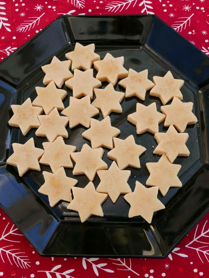 Marzipan Stars dusted with gold glitter and arranged on a black octagonal plate. It sits on a red Christmas table cloth