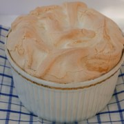 Black Forest Meringue Pudding viewed from above in a white souffle dish on a blue and white checked tea towel.