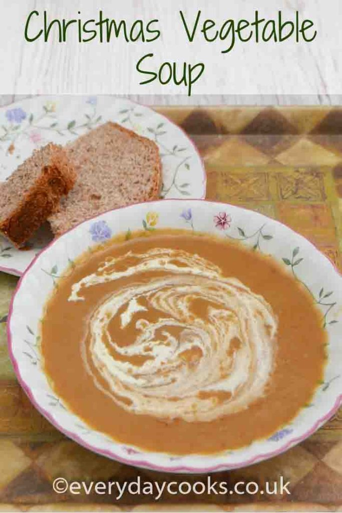 Christmas vegetable soup with a swirl of cream in a bowl with a piece of bread on a plate.
