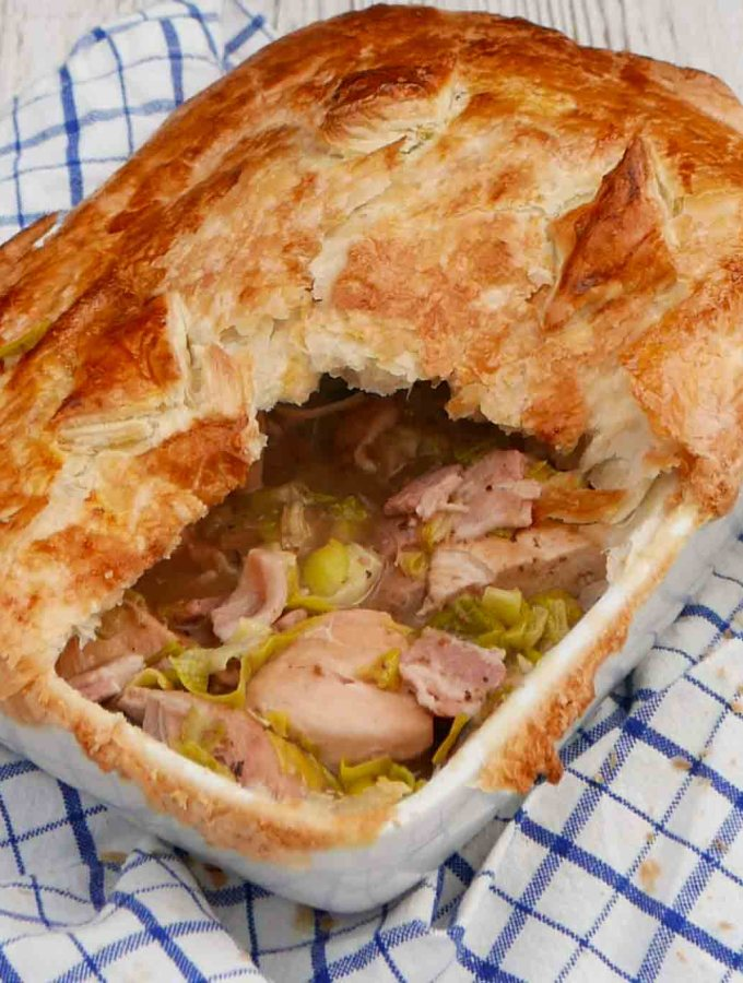 Chicken and leek pie with golden puff pastry on top. A slice has benn removed to show the filling.