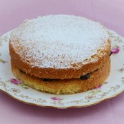 Victoria Sandwich cake with strawberry jam filling and icing sugar sprinkled on top. The cake is on a plate patterned with pink flowers and leaves.