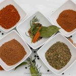 Top 5 Herb and Spice Mixes in small white bowls on a white plate