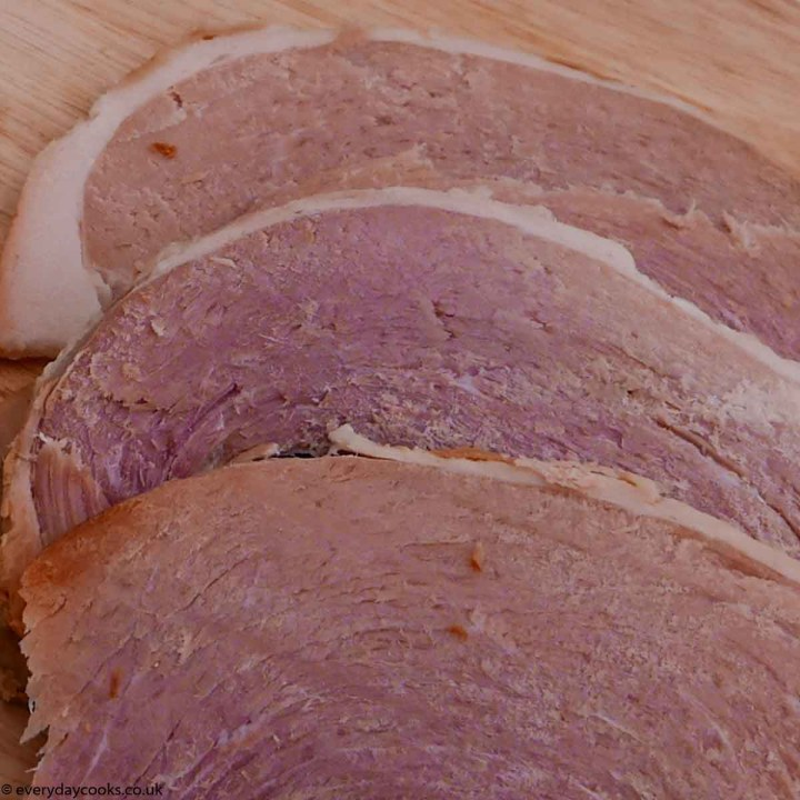 Slices of Slow Cooker Gammon on a board.