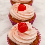 Three Triple Cherry Cupcakes on the worktop
