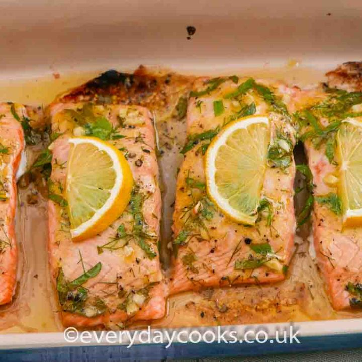 Four fillets of Baked Lemon Salmon garnished with slices of lemon and herbs in a gratin dish