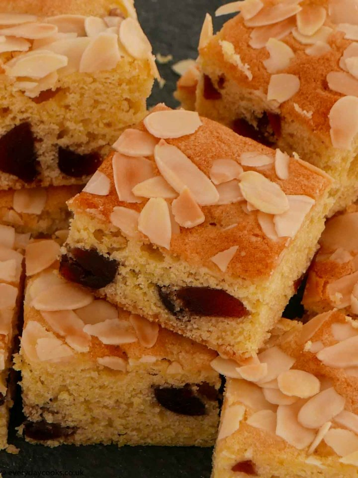 Squares of cherry and almond traybake on a slate
