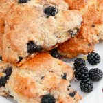 Blackberry Scones on a white plate with blackberries.