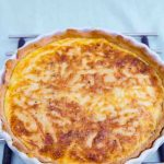 Cheese Quiche in a white flan dish on a blue cloth