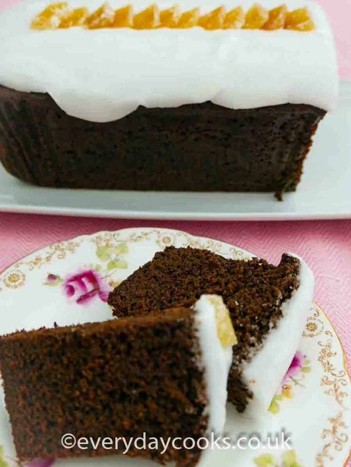 A slice of Iced Ginger Cake on a plate with the rest of the cake in the background