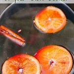 Mulled Wine with whole cinnamon and slices of orange in the Slow Cooker