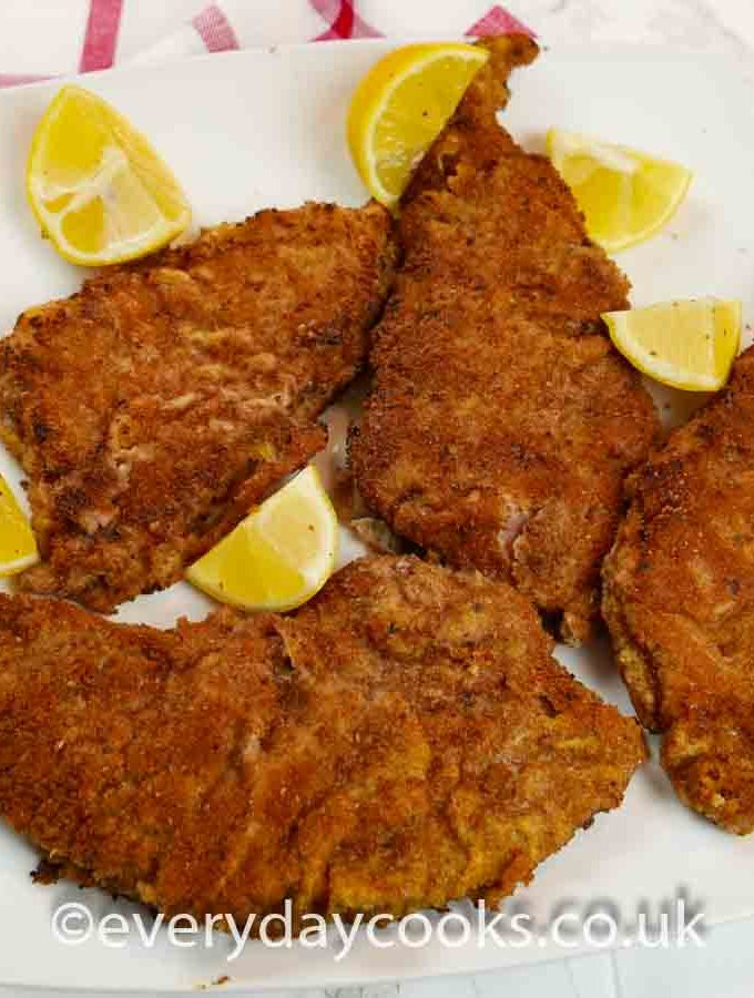 4 escalopes of Veal Milanese on a white plate with lemon wedges.