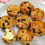Wholemeal Fruit Scones on a plate. One spread with butter.