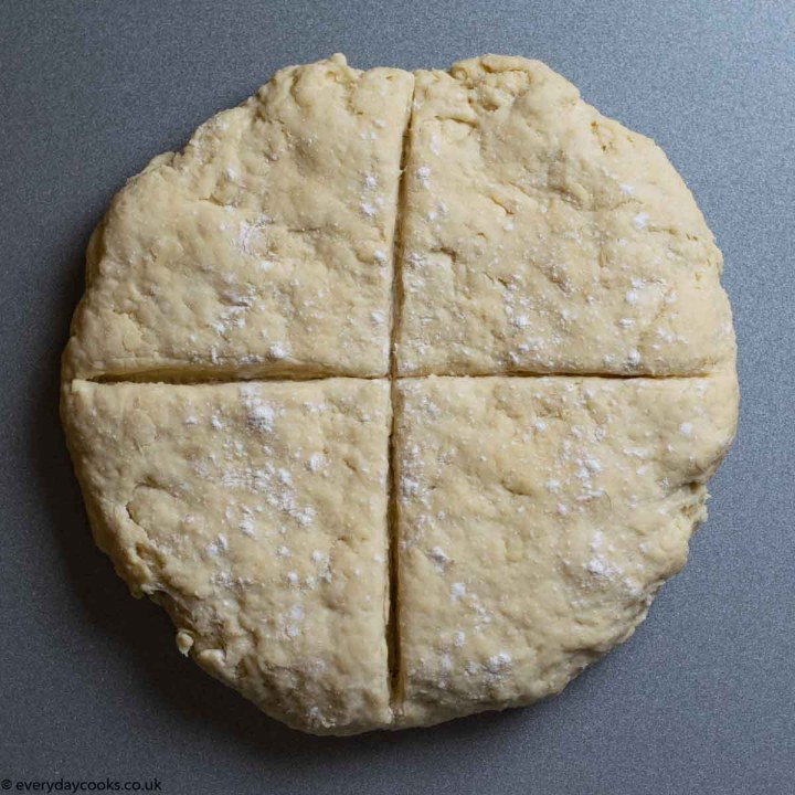 Dough flattened and scored with a cross ready for baking