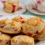 A plate of Cherry Scones with a teacup and plate with a single scone in the background on a blue cloth