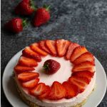 Easy Strawberry Cheesecake topped with sliced strawberries on a grey plate on a black worktop. 3 strawberries in the background.