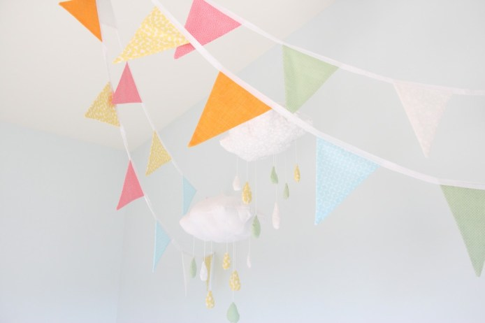 Orange, blue and green fabric flags in a baby's room