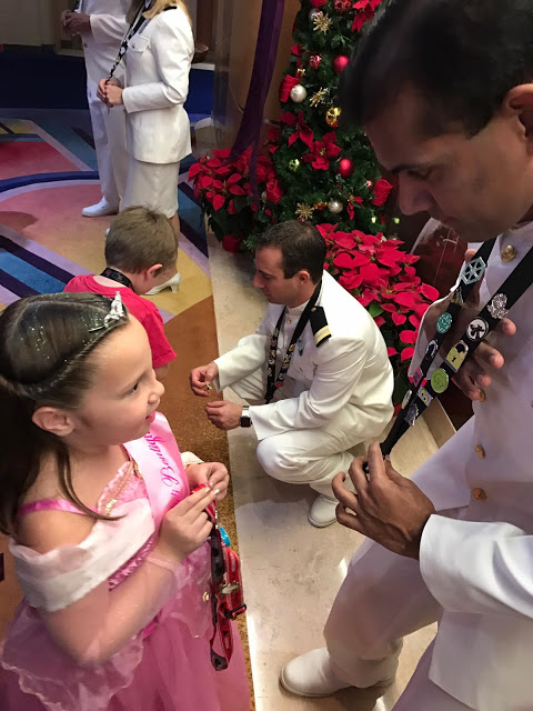 A girl trading pins with a Disney Cruise line cast member