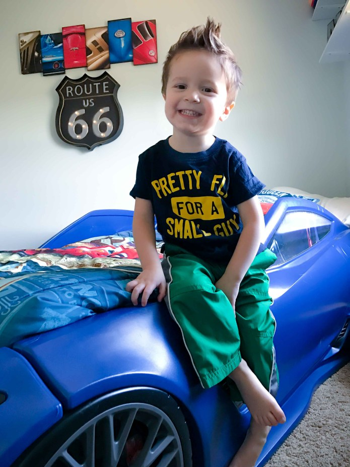 A toddler boy sitting on a blue race car bed.