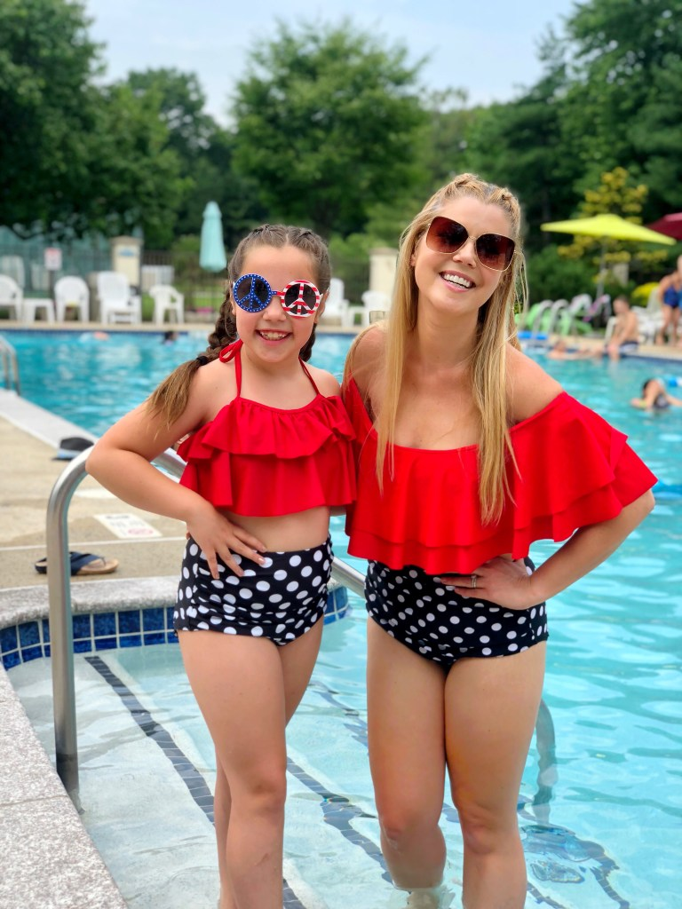 A mother and daughter smile at the pool in matching swimsuits
