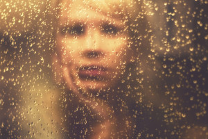 A person is looking at their reflection in a rainy window, touching their face