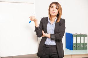 Persona de pie delante de una pizarra blanca con un marcador azul en la mano