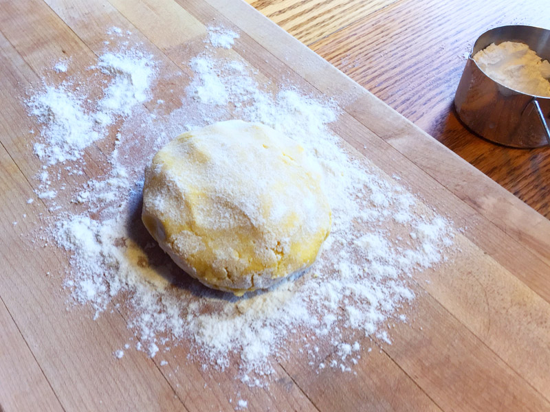 Gluten free noodle dough in a ball on a floured cutting board