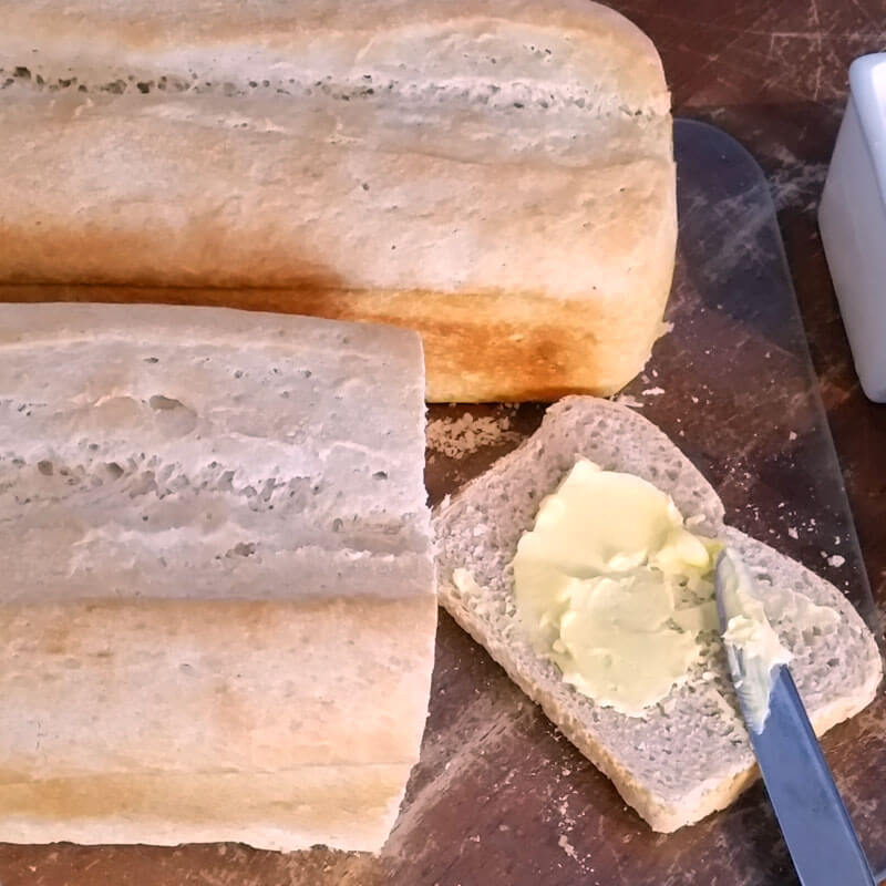 Fresh loaves of homemade sourdough bread, sliced with butter spread on top.