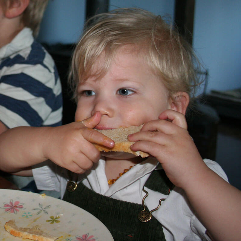 Little boy taking a big bite of a slice of homemade sourdough bread.