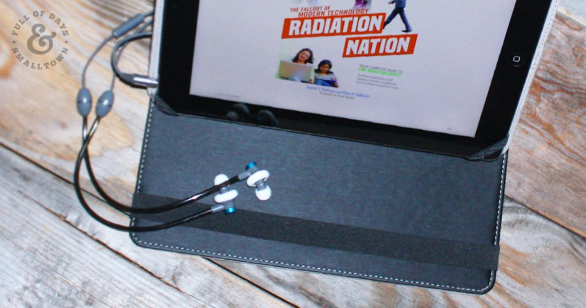 DefenderShield iPad cover and EMF blocking ear buds with Radiation Nation loaded on the screen