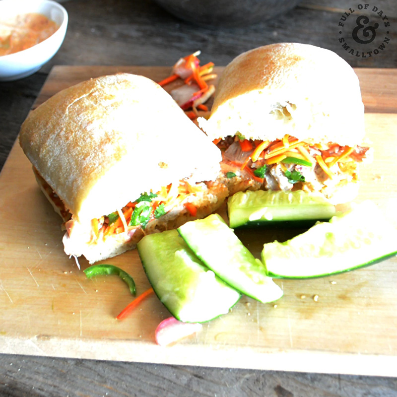Chicken Banh Mi assembled on a cutting board with smashed cucumber salad on the side.
