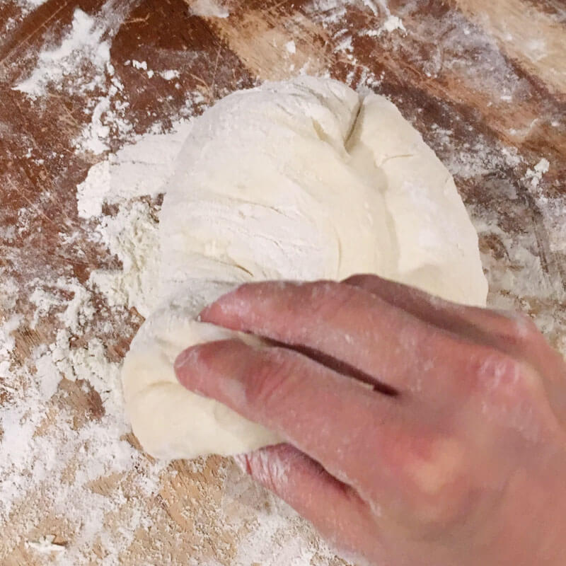Next, grab your dough at 6 o'clock, lift and pull toward the center of the dough.