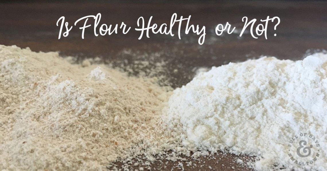 Ground Einkorn Grain next to unbleached white flour on a dark countertop.