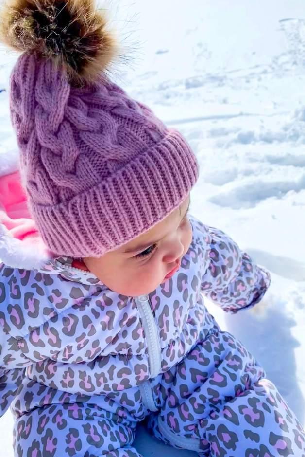 Winter Baby Necessities_baby in snowsuit sitting in the snow #babysnowsuit #winterbabyessentials
