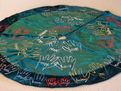 Fifteen years ago, I had the idea to paint two tiny sets of hands on a Christmas tree skirt. I had no idea what this tradition would become.