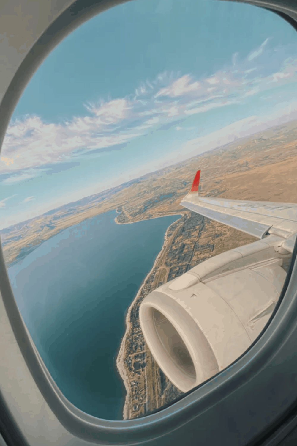 View from an airplane window looking out to water & land from the sky.