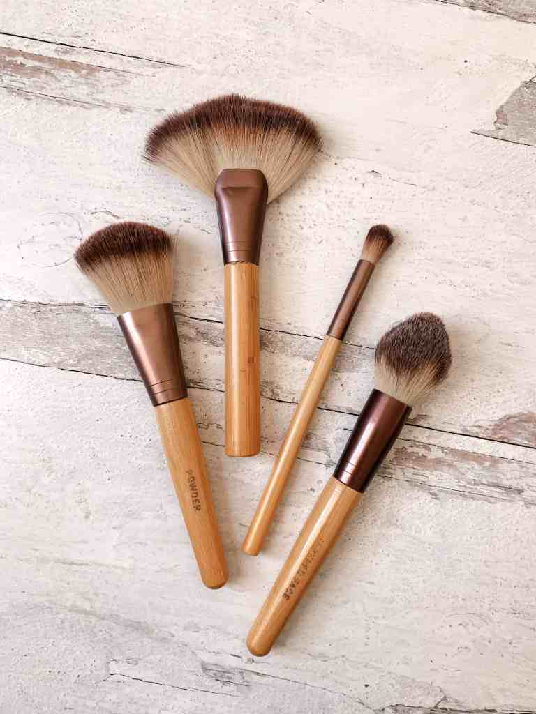 4 makeup brushes laying on a white wooden background