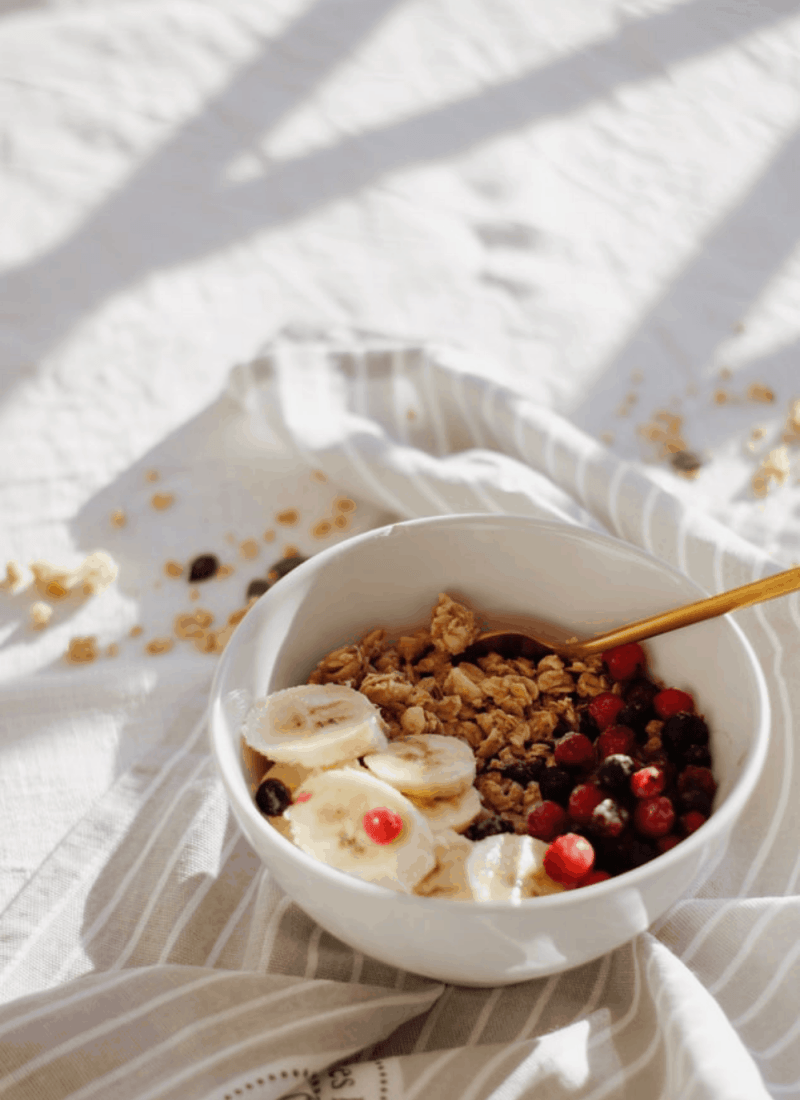 A bowl of granola & fruit on a surface.