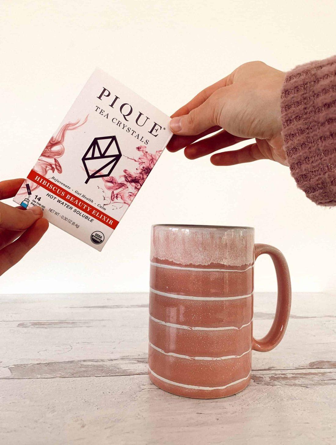 Holding up the Pique Tea Crystals box next to my mug.