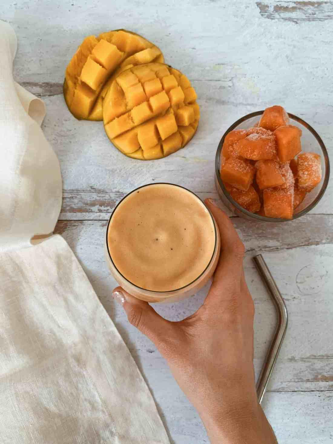 Hand holding a tropical mango smoothie.