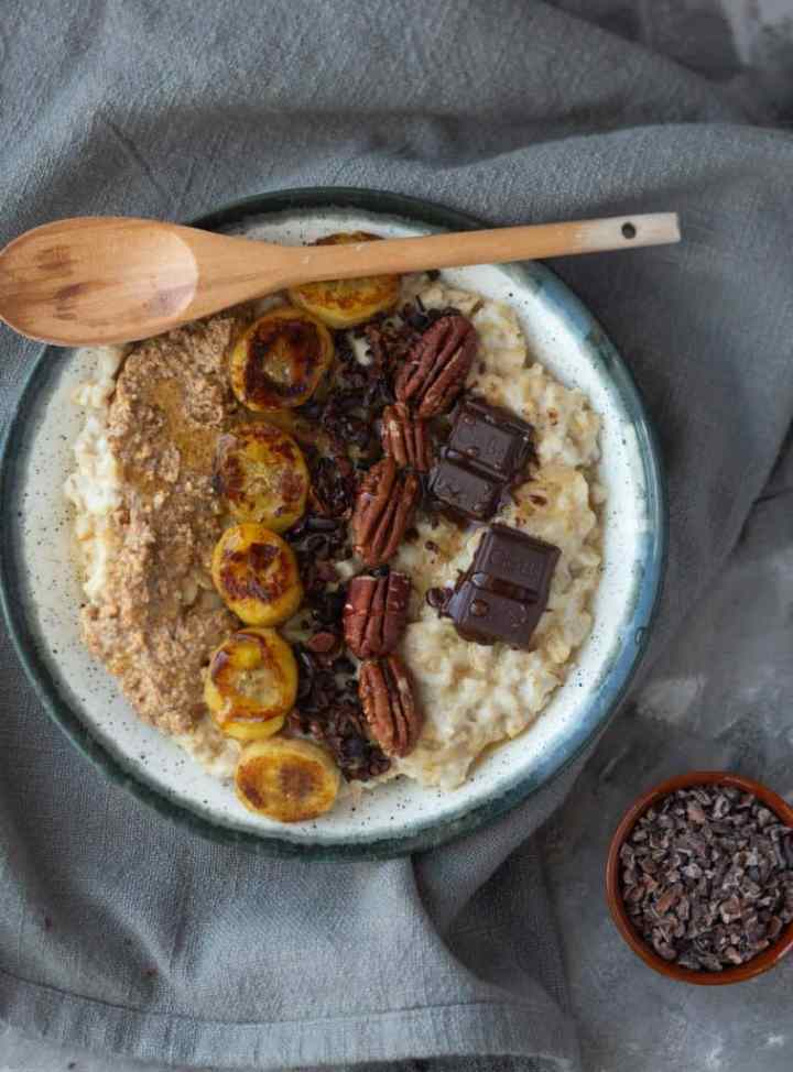 Banana Oatmeal with caramelized bananas in a plate with chocolate and nuts