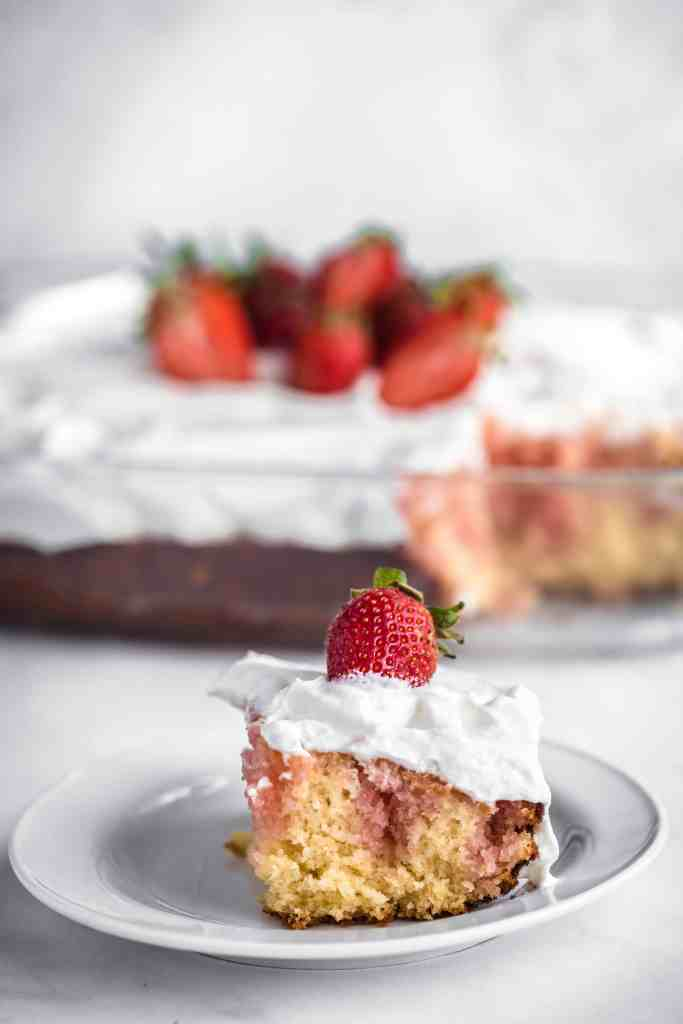 A slice of strawberry poke cake on a plate in front of the remainder of the cake
