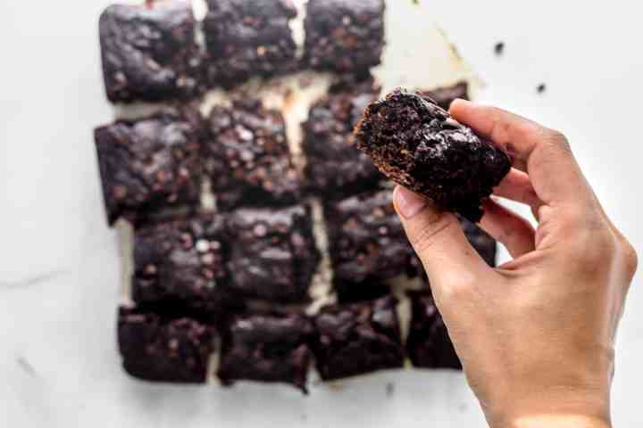 Hand holding a square of zucchini brownies